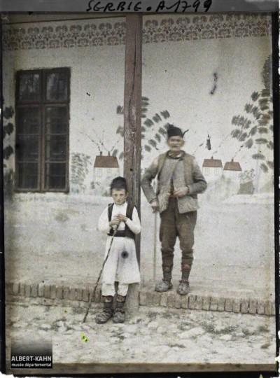 Osamdesetogodišnjak i mali dečak ispred kuće u Kumodražu na putu za Avalu 1913. g.